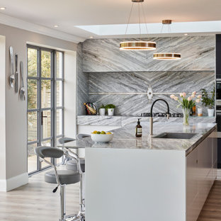 Photo of a large contemporary l-shaped open plan kitchen in Kent with flat-panel cabinets, grey splashback, marble splashback, stainless steel appliances, an island, grey floors and grey worktops.