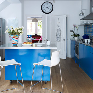 Contemporary enclosed kitchen designs - Inspiration for a contemporary galley medium tone wood floor enclosed kitchen remodel in London with a single-bowl sink, flat-panel cabinets, blue cabinets, multicolored backsplash, stainless steel appliances and an island