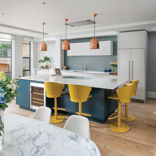 This is an example of a medium sized contemporary single-wall kitchen/diner in London with a submerged sink, flat-panel cabinets, an island, blue cabinets, blue splashback, integrated appliances, medium hardwood flooring and beige floors.