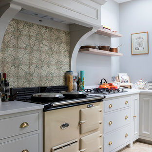This is an example of a medium sized country l-shaped kitchen/diner in London with a belfast sink, shaker cabinets, grey cabinets, composite countertops, green splashback, porcelain splashback, stainless steel appliances, limestone flooring, an island and beige floors.