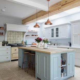 Idéer för att renovera ett mellanstort lantligt kök, med en rustik diskho, skåp i shakerstil, grå skåp, bänkskiva i koppar, grönt stänkskydd, stänkskydd i porslinskakel, rostfria vitvaror, kalkstensgolv, en köksö och beiget golv