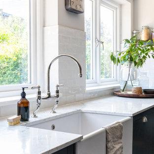 ロンドンの広いヴィクトリアン調のおしゃれなキッチン (ドロップインシンク、シェーカースタイル扉のキャビネット、青いキャビネット、大理石カウンター、白いキッチンパネル、セラミックタイルのキッチンパネル、パネルと同色の調理設備、ラミネートの床、白いキッチンカウンター) の写真