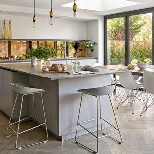 Modern inredning av ett stort grå grått kök, med en undermonterad diskho, släta luckor, grå skåp, bänkskiva i kvartsit, stänkskydd med metallisk yta, spegel som stänkskydd, vinylgolv, en köksö och beiget golv
