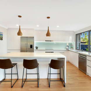 Design ideas for a contemporary l-shaped kitchen in Gold Coast - Tweed with a double-bowl sink, flat-panel cabinets, white cabinets, glass sheet splashback, stainless steel appliances, dark hardwood floors, with island, beige floor and white benchtop.