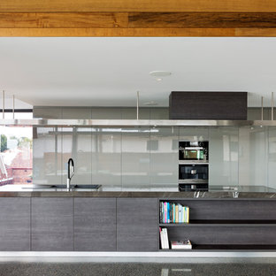Inspiration for a contemporary galley open plan kitchen in Brisbane with a drop-in sink, flat-panel cabinets, grey cabinets, black appliances, concrete floors, an island, grey floor and grey benchtop.