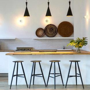 ニューヨークの広いコンテンポラリースタイルのおしゃれなキッチン (木材カウンター、フラットパネル扉のキャビネット、白いキッチンパネル、サブウェイタイルのキッチンパネル、パネルと同色の調理設備、淡色無垢フローリング、ドロップインシンク、白いキャビネット、ベージュの床、茶色いキッチンカウンター) の写真