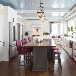 Large traditional separate kitchen in Omaha with a farmhouse sink, shaker cabinets, white cabinets, white splashback, stainless steel appliances, medium hardwood floors and multiple islands.