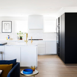 This is an example of a contemporary l-shaped open plan kitchen in Sydney with an undermount sink, flat-panel cabinets, white cabinets, white splashback, medium hardwood floors, with island, brown floor and white benchtop.