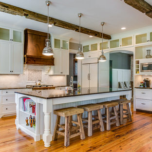 シャーロットの大きいヴィクトリアン調のおしゃれなキッチン (落し込みパネル扉のキャビネット、白いキャビネット、マルチカラーのキッチンパネル、パネルと同色の調理設備、石タイルのキッチンパネル、エプロンフロントシンク、無垢フローリング、茶色い床) の写真