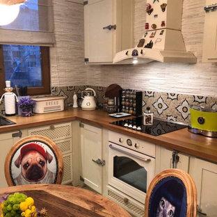 他の地域の中サイズのシャビーシック調のおしゃれなキッチン (インセット扉のキャビネット、ベージュのキャビネット、木材カウンター、マルチカラーのキッチンパネル、カラー調理設備、大理石の床、マルチカラーの床、エプロンフロントシンク、モザイクタイルのキッチンパネル) の写真