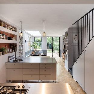 Exemple d'une cuisine parallèle tendance de taille moyenne avec un plan de travail en inox, un îlot central, un évier encastré, un placard à porte plane, des portes de placard blanches, un sol en bois clair, un sol beige et un plan de travail noir.