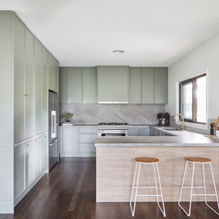 Design ideas for a mid-sized scandinavian galley open plan kitchen in Other with an undermount sink, shaker cabinets, green cabinets, solid surface benchtops, grey splashback, stone slab splashback, stainless steel appliances, dark hardwood floors, with island, black floor, grey benchtop and recessed.