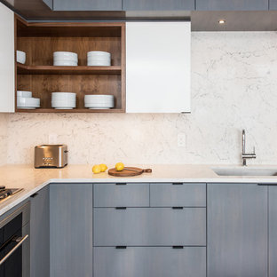 Eat-in kitchen - small contemporary l-shaped eat-in kitchen idea in New York with an undermount sink, flat-panel cabinets, gray cabinets, quartz countertops, white backsplash, stone slab backsplash, no island, white countertops and stainless steel appliances