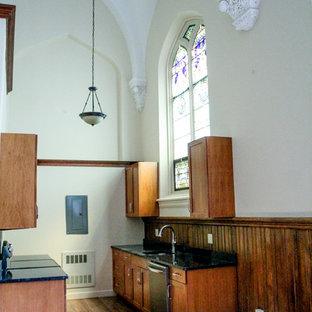 ボストンのおしゃれなキッチン (シングルシンク、レイズドパネル扉のキャビネット、中間色木目調キャビネット、御影石カウンター、シルバーの調理設備、濃色無垢フローリング) の写真