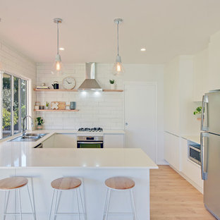 Design ideas for a beach style u-shaped separate kitchen in Sunshine Coast with a drop-in sink, flat-panel cabinets, white cabinets, white splashback, subway tile splashback, stainless steel appliances, light hardwood floors, a peninsula and beige floor.