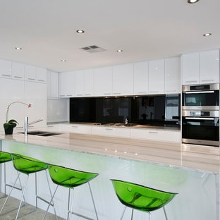 Mid-sized modern u-shaped open plan kitchen in Perth with a double-bowl sink, flat-panel cabinets, white cabinets, granite benchtops, black splashback, glass sheet splashback, stainless steel appliances, marble floors and with island.