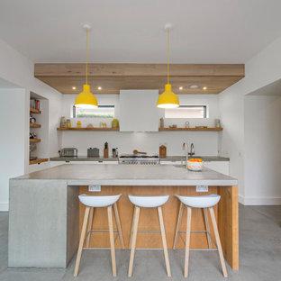 Стильный дизайн: кухня-гостиная среднего размера в современном стиле с накладной раковиной, плоскими фасадами, белыми фасадами, столешницей из бетона, белым фартуком, техникой из нержавеющей стали, бетонным полом, островом, серым полом, серой столешницей и потолком из вагонки - последний тренд