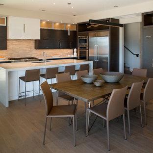 他の地域の広いコンテンポラリースタイルのおしゃれなキッチン (アンダーカウンターシンク、フラットパネル扉のキャビネット、濃色木目調キャビネット、クオーツストーンカウンター、シルバーの調理設備、無垢フローリング、マルチカラーのキッチンパネル、ボーダータイルのキッチンパネル) の写真
