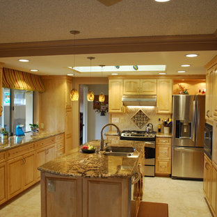 Traditional galley eat-in kitchen in Sacramento with an undermount sink, raised-panel cabinets, light wood cabinets, granite benchtops, beige splashback, stone tile splashback, stainless steel appliances, porcelain floors and with island.