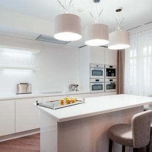 Свежая идея для дизайна: прямая кухня в современном стиле с плоскими фасадами, белыми фасадами, белым фартуком, паркетным полом среднего тона, островом, обеденным столом и техникой из нержавеющей стали - отличное фото интерьера