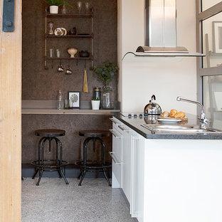 Idées déco pour une petite cuisine ouverte industrielle en U avec un évier 2 bacs, un placard à porte plane, des portes de placard blanches, un plan de travail en surface solide, une crédence marron, une crédence en dalle de pierre, un électroménager en acier inoxydable, un sol en terrazzo, un îlot central, un sol gris et un plan de travail marron.