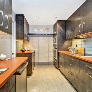 Inspiration for a small contemporary galley separate kitchen in Ottawa with a drop-in sink, flat-panel cabinets, dark wood cabinets, laminate benchtops, blue splashback, glass tile splashback, porcelain floors, beige floor and orange benchtop.