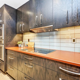 Photo of a small contemporary galley separate kitchen in Ottawa with a drop-in sink, flat-panel cabinets, dark wood cabinets, laminate benchtops, blue splashback, glass tile splashback, porcelain floors, beige floor and orange benchtop.