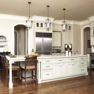Idee per una grande cucina design con elettrodomestici in acciaio inossidabile, ante in stile shaker, ante beige, top in marmo, paraspruzzi bianco, pavimento in legno massello medio, isola, lavello sottopiano e paraspruzzi con piastrelle in ceramica