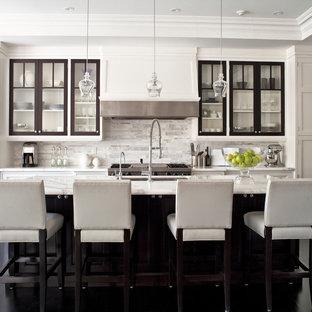 トロントのII型トランジショナルスタイルのキッチンの画像 (白いキッチンパネル、大理石カウンター、アンダーカウンターシンク、白いキャビネット、ガラス扉のキャビネット、パネルと同色の調理設備、大理石の床、白いキッチンカウンター)