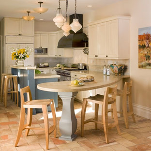This is an example of a mid-sized contemporary l-shaped open plan kitchen in San Francisco with a farmhouse sink, recessed-panel cabinets, white cabinets, limestone benchtops, beige splashback, stone tile splashback, panelled appliances, terra-cotta floors and with island.
