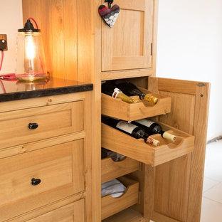 Idee per una cucina abitabile vittoriana con lavello stile country, ante a filo, ante in legno chiaro e top in granito