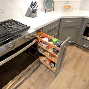オレンジカウンティの巨大なコンテンポラリースタイルのおしゃれなキッチン (ダブルシンク、落し込みパネル扉のキャビネット、グレーのキャビネット、クオーツストーンカウンター、グレーのキッチンパネル、磁器タイルのキッチンパネル、シルバーの調理設備、ラミネートの床、ベージュの床、グレーのキッチンカウンター) の写真