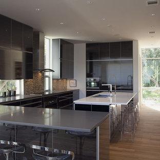 オースティンの広いコンテンポラリースタイルのおしゃれなキッチン (フラットパネル扉のキャビネット、黒いキャビネット、マルチカラーのキッチンパネル、トリプルシンク、クオーツストーンカウンター、モザイクタイルのキッチンパネル、シルバーの調理設備、無垢フローリング) の写真