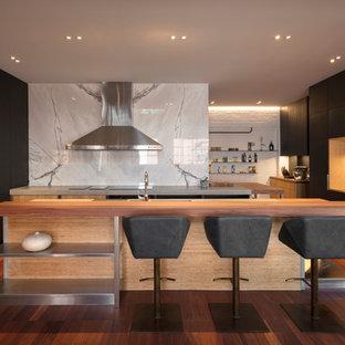 メルボルンの大きいコンテンポラリースタイルのおしゃれなキッチン (アンダーカウンターシンク、フラットパネル扉のキャビネット、黒いキャビネット、コンクリートカウンター、白いキッチンパネル、大理石のキッチンパネル、シルバーの調理設備、無垢フローリング、茶色い床、グレーのキッチンカウンター) の写真