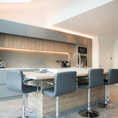 Example of a mid-sized trendy single-wall porcelain tile and beige floor open concept kitchen design in Dublin with quartzite countertops, an island, flat-panel cabinets, beige backsplash, glass sheet backsplash and stainless steel appliances