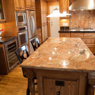 Klassische Küche in L-Form mit Vorratsschrank, Waschbecken, profilierten Schrankfronten, hellbraunen Holzschränken, Granit-Arbeitsplatte, Küchengeräten aus Edelstahl, braunem Holzboden und Kücheninsel in Portland