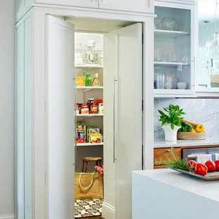 Kitchen pantry - mid-sized contemporary galley dark wood floor kitchen pantry idea in Atlanta with glass-front cabinets, white cabinets, an undermount sink, solid surface countertops, gray backsplash, stainless steel appliances and an island