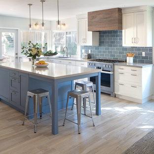 サンディエゴの広いビーチスタイルのおしゃれなキッチン (アンダーカウンターシンク、シェーカースタイル扉のキャビネット、青いキャビネット、クオーツストーンカウンター、青いキッチンパネル、磁器タイルのキッチンパネル、シルバーの調理設備、磁器タイルの床、ベージュの床、グレーのキッチンカウンター) の写真