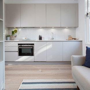 ロンドンの北欧スタイルのおしゃれなキッチン (フラットパネル扉のキャビネット、グレーのキャビネット、グレーのキッチンパネル、淡色無垢フローリング) の写真