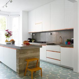 Modelo de cocina lineal, contemporánea, grande, abierta, con encimera de cemento, salpicadero verde, una isla, fregadero sobremueble, armarios con paneles lisos, puertas de armario blancas, salpicadero de azulejos de cemento y suelo azul
