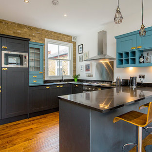 Photo of a medium sized traditional u-shaped kitchen in London with a double-bowl sink, metallic splashback, stainless steel appliances, medium hardwood flooring, a breakfast bar, brown floors, black worktops, shaker cabinets and blue cabinets.