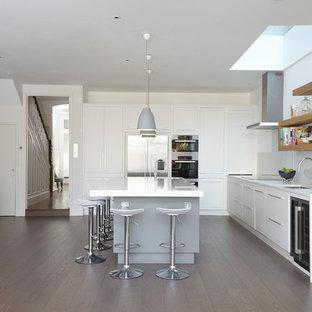 Стильный дизайн: угловая кухня в современном стиле с врезной раковиной, плоскими фасадами, белыми фасадами, белым фартуком, фартуком из стекла, техникой из нержавеющей стали, паркетным полом среднего тона и островом - последний тренд