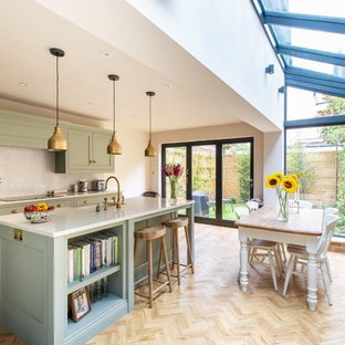 This is an example of a medium sized traditional single-wall kitchen/diner in Kent with green cabinets, white splashback, light hardwood flooring, an island, beige floors, white worktops and shaker cabinets.