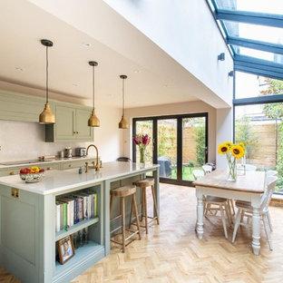 Foto di una cucina tradizionale di medie dimensioni con ante verdi, paraspruzzi bianco, parquet chiaro, isola, pavimento beige, top bianco e ante in stile shaker