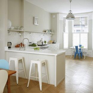 Medium sized traditional l-shaped kitchen/diner in London with a submerged sink, white cabinets, composite countertops, white splashback, metro tiled splashback, stainless steel appliances, a breakfast bar, open cabinets and medium hardwood flooring.