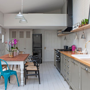 Inspiration for a romantic single-wall kitchen/diner in London with a built-in sink, shaker cabinets, grey cabinets, wood worktops, white splashback, metro tiled splashback, black appliances, painted wood flooring, no island, white floors, brown worktops and a vaulted ceiling.