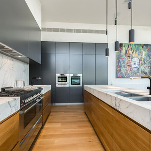 Inspiration for a contemporary u-shaped kitchen in Geelong with flat-panel cabinets, with island, an undermount sink, medium wood cabinets, grey splashback, stainless steel appliances, medium hardwood floors and beige floor.