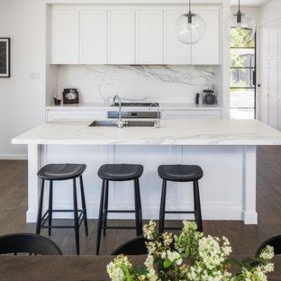 Стильный дизайн: угловая кухня-гостиная в современном стиле с врезной раковиной, фасадами в стиле шейкер, белыми фасадами, столешницей из кварцевого агломерата, белым фартуком, фартуком из мрамора, техникой из нержавеющей стали, темным паркетным полом, островом, белой столешницей и коричневым полом - последний тренд