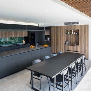 Inspiration for a modern l-shaped eat-in kitchen in Perth with a double-bowl sink, flat-panel cabinets, black cabinets, window splashback, with island, grey floor and black benchtop.