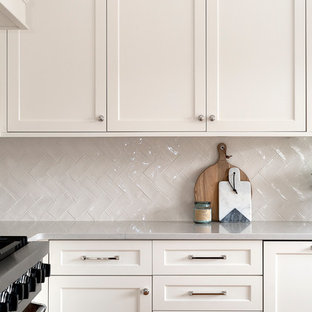 Mid-sized eat-in kitchen designs - Mid-sized l-shaped light wood floor eat-in kitchen photo in Chicago with a farmhouse sink, shaker cabinets, white cabinets, quartz countertops, white backsplash, ceramic backsplash, paneled appliances and an island